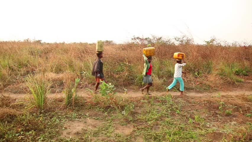 VILLAGE OF BWE, DEMOCRATIC REPUBLIC OF THE CONGO - JULY 14, 2012: Unidentified girls carrying water from well. (For editorial use only.)