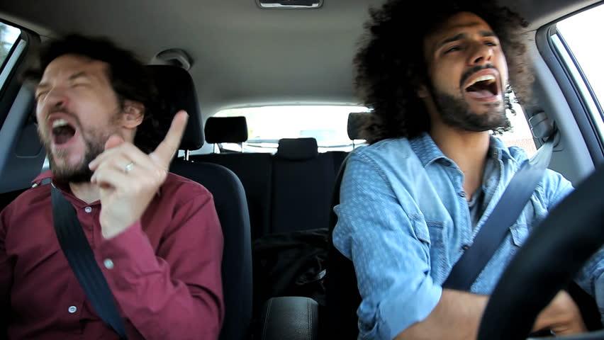 Two men in car having fun singing and dancing