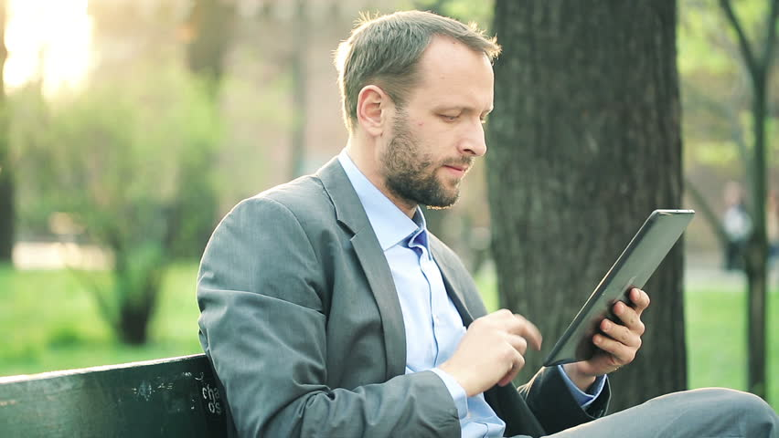 Young businessman with tablet computer sitting on bench in the park