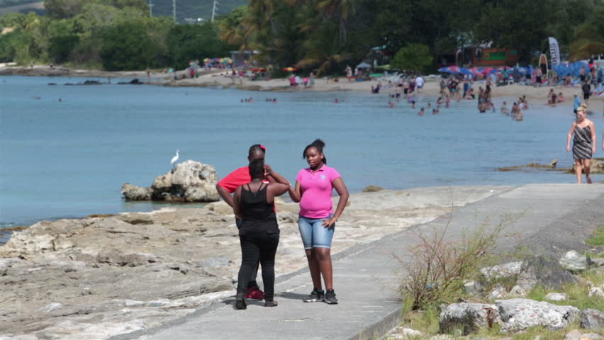 ST CROIX - JAN 2014: Tourism is main source of income to Island. St Croix American Virgin Islands girls friends by beach. Discovered by Christoper Columbus in 1493. Beach recreation and fun.