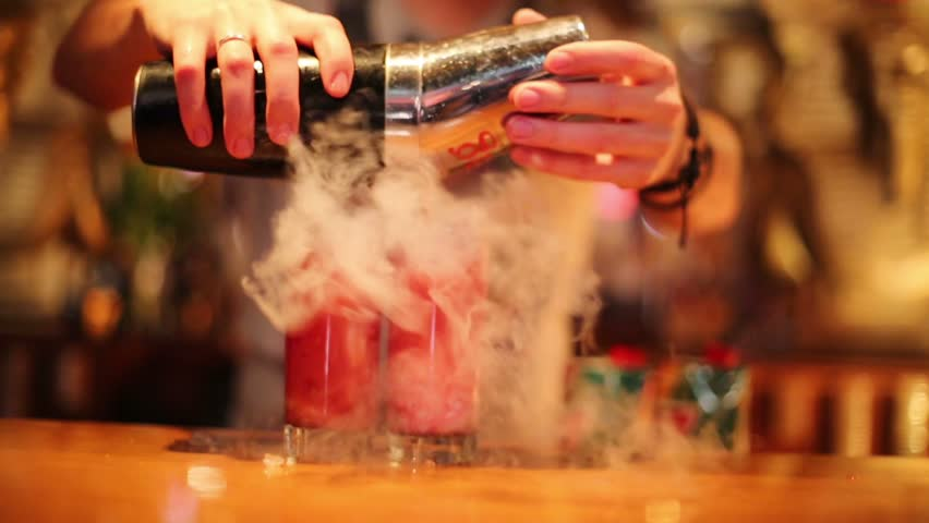Hands of young bartender preparing two red cocktails with smoke in night club