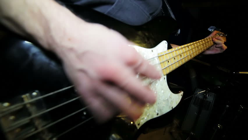 Male rock bass guitarist playing electric bass guitar in studio