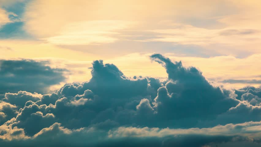 4K. Beautiful epic scenic cumulus clouds rolling over sky background backlit by sunset. Timelapse