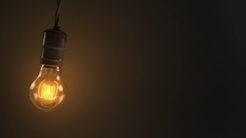 An animated loop of a single swinging vintage incandescent lightbulb over a dark warm background
