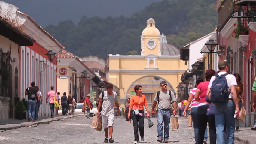 ANTIGUA GUATEMALA,GUATEMALA,2012:Tourist industry.Tourists on the streets of the colonial small town.Perspective of cobbled streets with colonial architecture style  buildings in a picturesque valley.