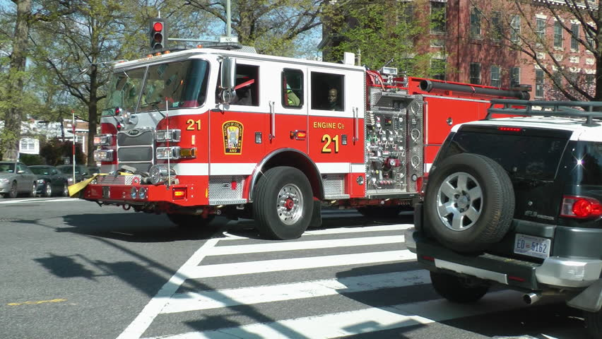 WASHINGTON, DC - APRIL 2014: Fire Department engine honks through stubborn traffic, turns corner, siren.  Washington, DC.  Engines are staffed with trained EMTs, often arriving before ambulance.