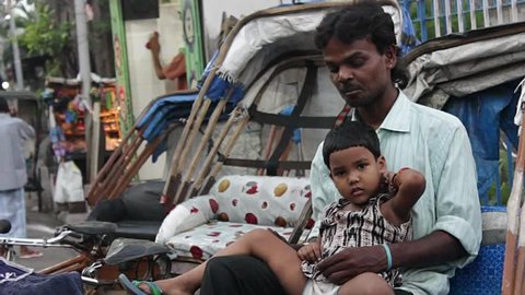 A father and his daughter sit in a rickshaw in Calcutta / Kolkata, Bengal India.  HD 1920 by 1080. Still shot.