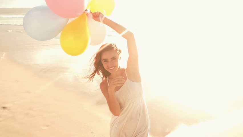 Girl with balloons at beach