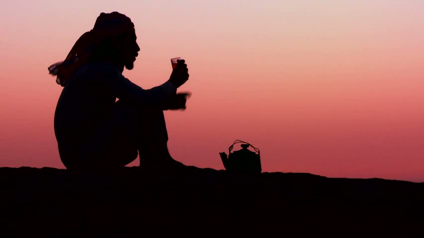 WADI RUM, JORDAN CIRCA 2013 - A Bedouin man pours tea in silhouette against the sunset.