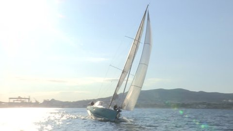 Sailing boat navigating in the sea with open sails