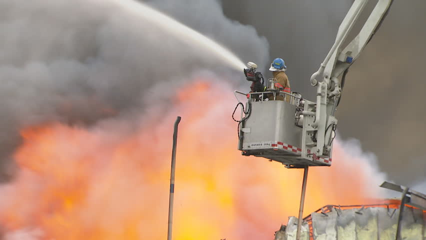 Fireman fighting a fire with heavy smoke frames at a factory storage in Korea