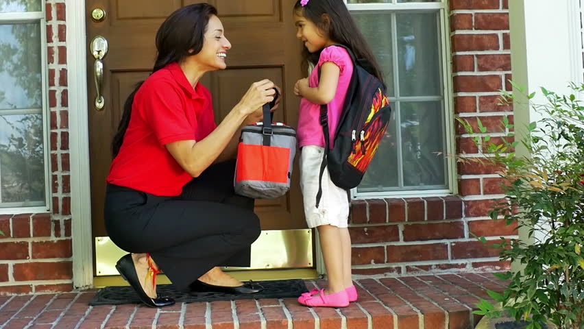 A little Hispanic girl wearing a backpack gives her mother a little kiss after getting her lunch bag and a cheerful send off to school. slow motion.