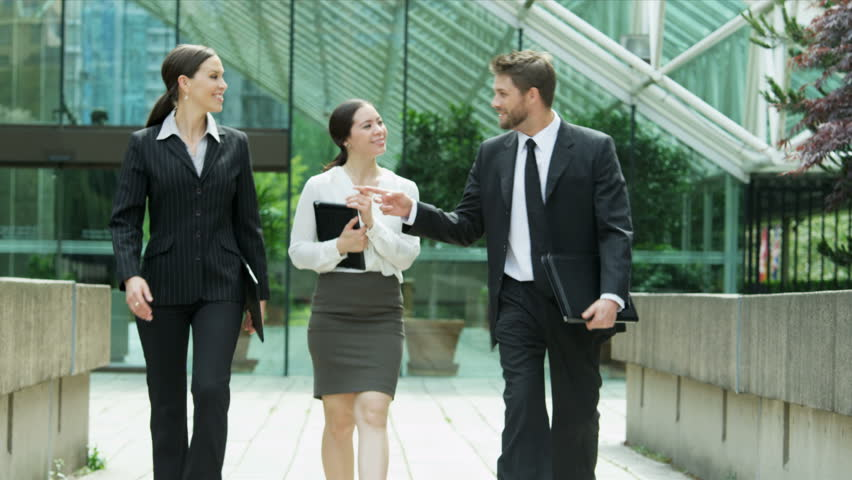 Outdoors Downtown Meeting Multi Ethnic Business Managers - Young Caucasian Asian Chinese male female business managers carrying portfolios tablet walking outside modern glass downtown office buildings