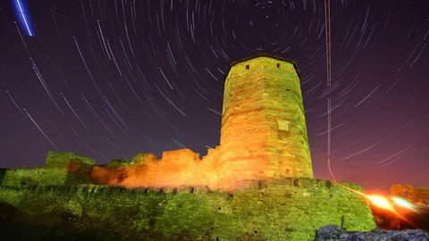Old stone tower on starry night skies background - star trails time lapse