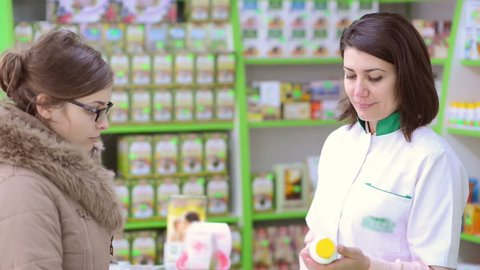 Young female pharmacist in a drugstore having conversation with a customer