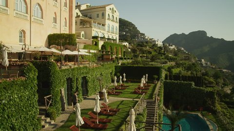 Wide Shot Pan People walking down stairs by mansion on cliff / Ravello, Campania, Italy