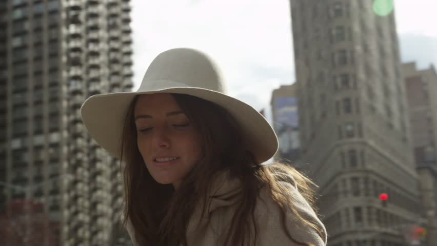 Close up tracking shot of smiling young woman looking up at trees and high  rises /