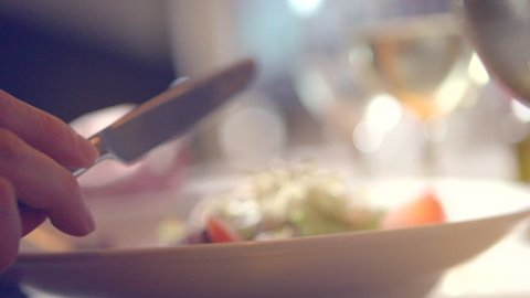 Dinner in a restaurant. Person eating delicious salad. Young man enjoying dinner. Healthy food. Fresh vegetable salad. Close up. Slow motion video footage. Slowmo. Slow-mo. High speed camera shot