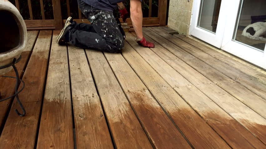 A deck balcony being oiled with a stain and protector by hand by brush.
