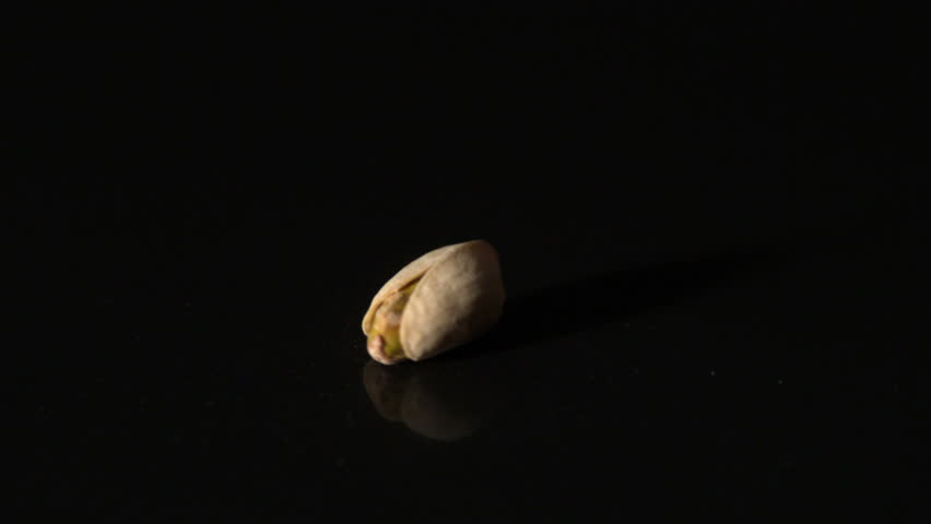 Pistachio nut spinning on black surface in slow motion | Shutterstock HD Video #6431408