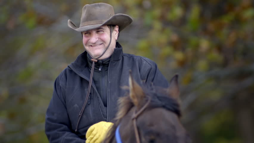 Close up of a smiling cowboy on horseback, in slow motion