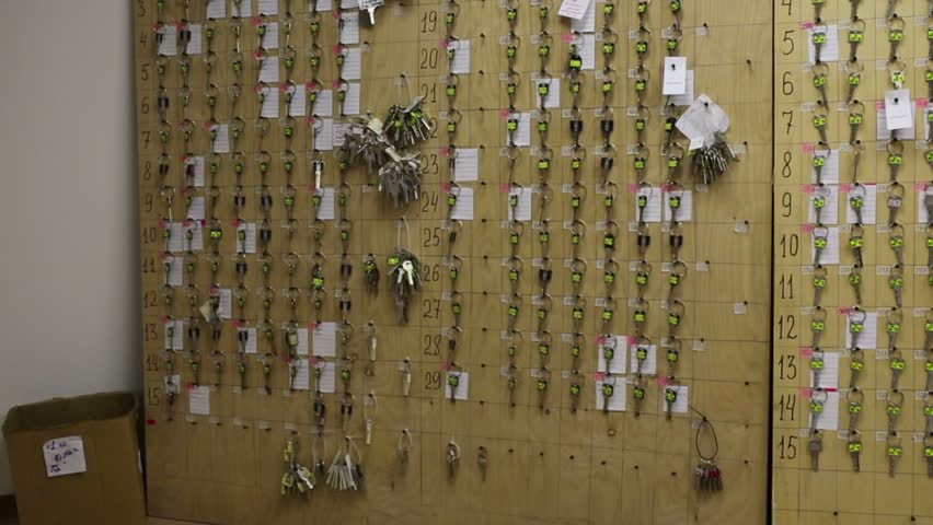 Wall with many rows of keys with numbers, labels and stickers in dispatch of residential complex