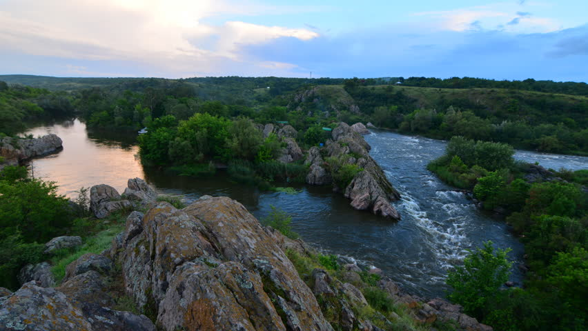 Top view from the mountains to the river canyon - the current turbulent river at sunset, forest island and smoke time lapse