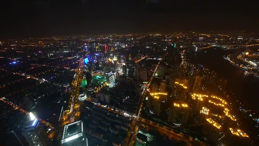 Elevated View Of Brightly Lit High Rise Buildings With River At Night In Shanghai