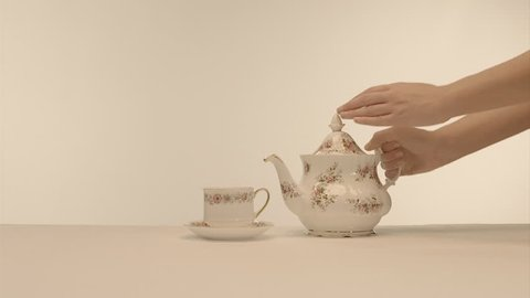 Afternoon tea - Mid shot of traditional vintage english bone china teapot pouring tea into teacup and saucer on plain white background.