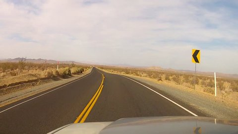 The point of view of someone driving a vehicle on the newly paved section of historic route 66 as it travels through the Mojave desert between Victorville and Barstow, CA.