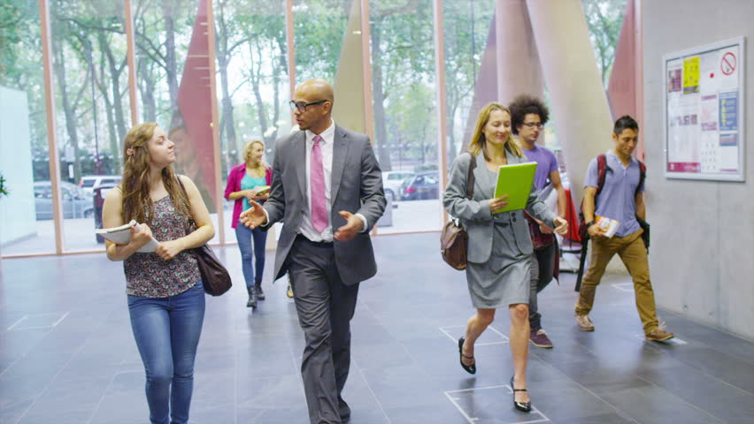 Cheerful student arrives for an interview at large modern college or university. | Shutterstock HD Video #6556034