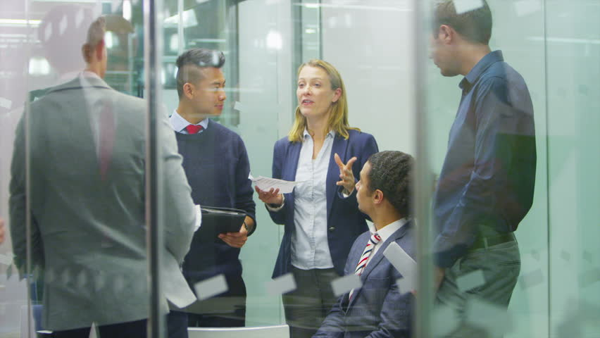 Attractive young business team in a meeting in modern city office. | Shutterstock HD Video #6556676