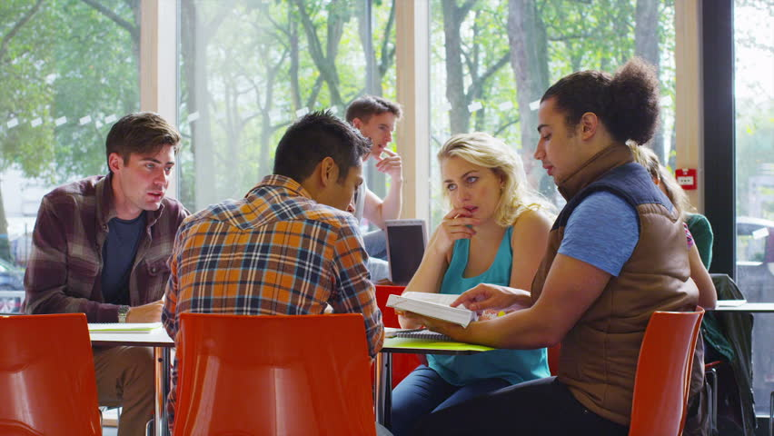 Cheerful diverse student group chatting & working together in college cafe area | Shutterstock HD Video #6557996