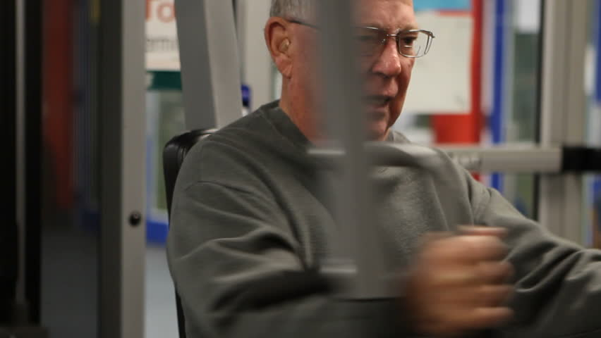 Elderly man does a chest muscle workout at the fitness club.