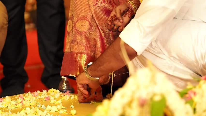 Groom Puts A Ring On The Brides Toe During A South Indian Wedding