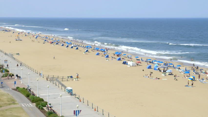 Wide birds-eye view of the famous Virginia Beach boardwalk and beach, with tourists on vacation.
