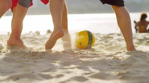 Friends play soccer on the beach