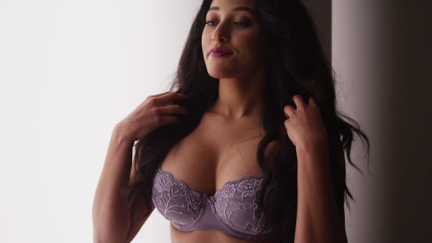 93e6ce97c4d Sultry Mexican woman standing in lingerie by window