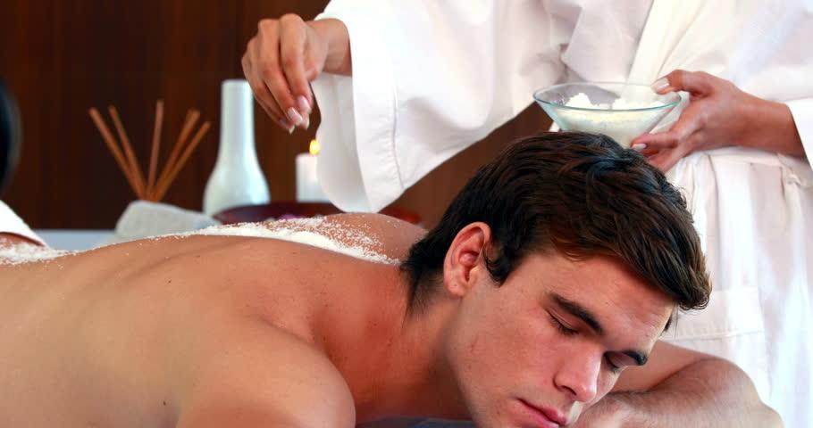 Handsome man getting a salt scrub treatment at the spa