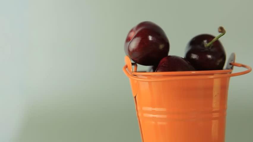 Juicy, ripe cherries. Full bucket of cherries rotates clockwise strelkke on a gray background. Vitamins, sweet juice. Healthy lifestyle.   Shutterstock HD Video #6652214