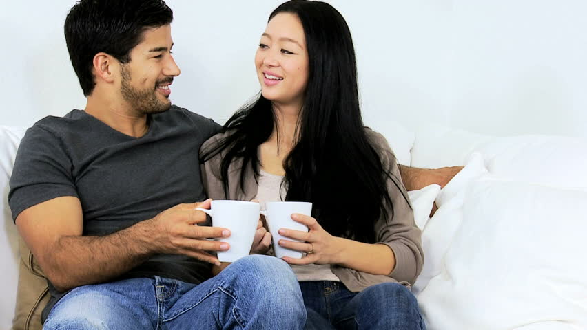 Attractive young ethnic couple wearing casual clothes sitting together  talking home sofa drinking coffee close up