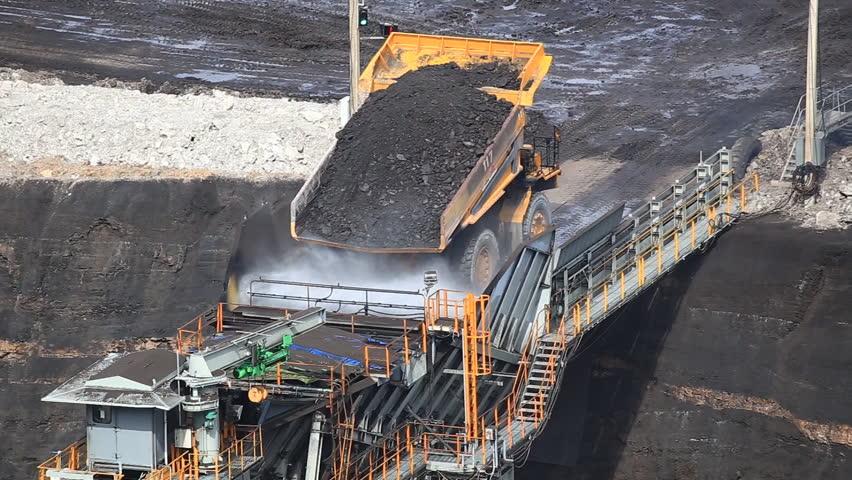 heavy construction tipper trucks dump coal to the conveyor at coal mine