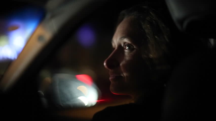 Driving at night - passenger seat . Woman in her early 30s looking at driver in a teasing manner. Casual, real life, candid take of girl flirting with man