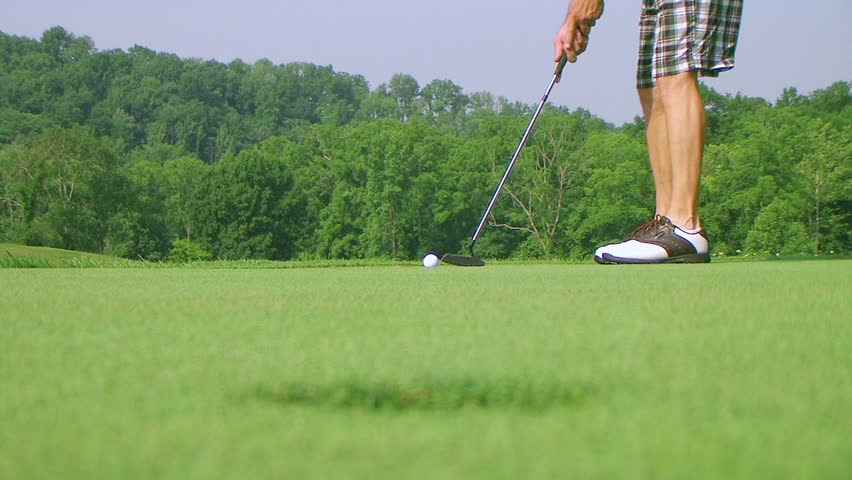 Close-up of golfer using putter to sink long putt into hole, rack focus with shotgun audio.