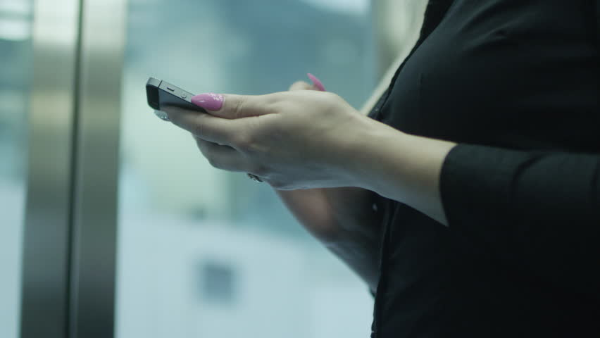 Woman is Using Mobile Phone in Elevator.  | Shutterstock HD Video #6766054