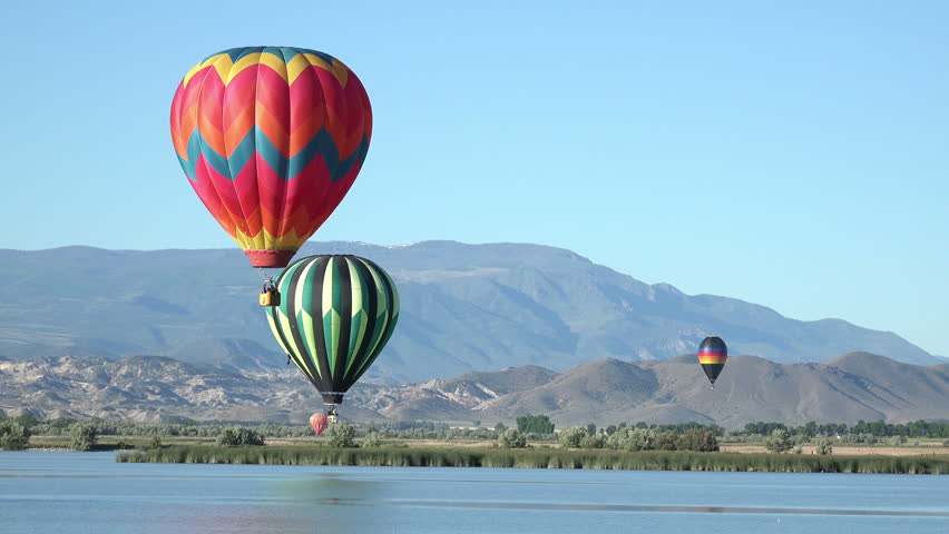 SALINA, UTAH - JUN 2014: Mountain valley lake hot air balloons flight. Annual event bring tourism and money to rural community. Flying from farms passengers enjoy view of mountain valley.