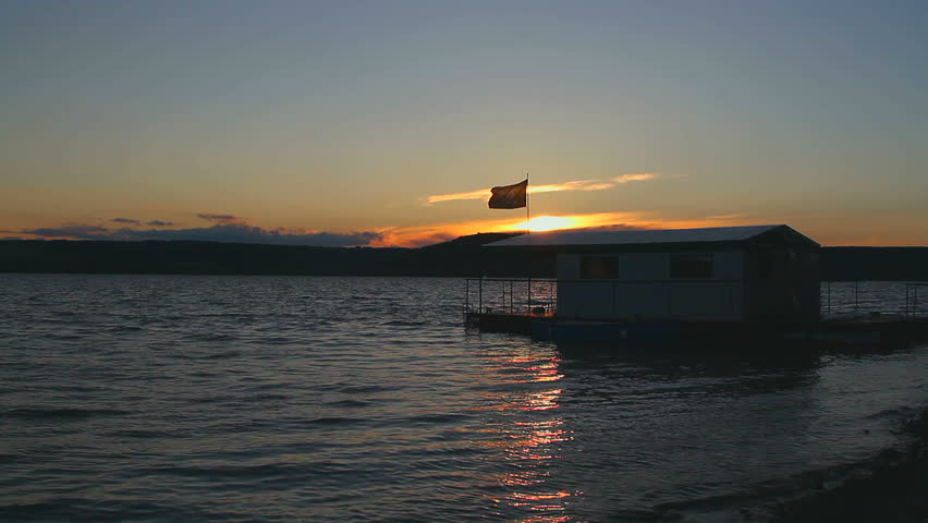 houseboat, house on the water, houseboat with Jolly Roger on a sunset, A pirate flag on a houseboat at sunset, Silhouette of the Houseboat at sunset, man on a houseboat