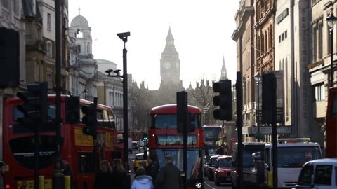 LONDON, CIRCA MARCH 2014 - Red London buses and traffic drive on a street with Big Ben in the background. Dolly/tracking movement