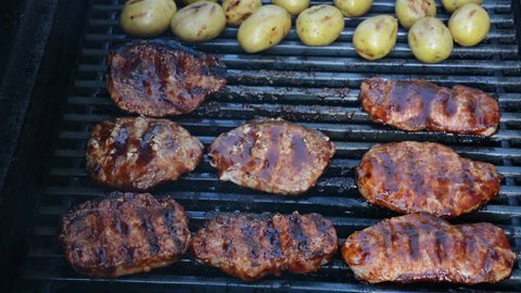 Barbecue pork chops being flipped on a grill with potatoes. 1080p BBQ grilling shots.