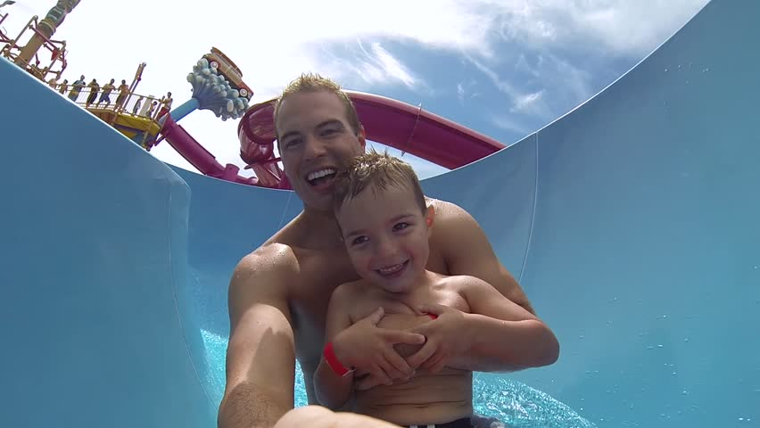 Attractive athletic and healthy father going down a bright colored water slide with his young son on a clear beautiful Summer afternoon.